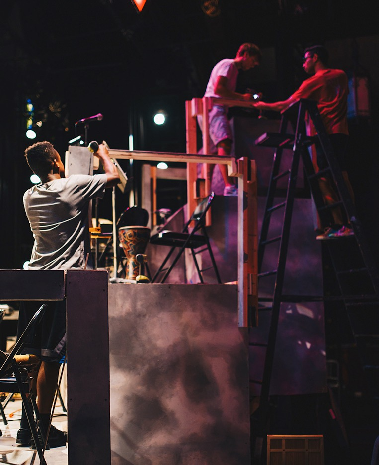 A Mask and Wig stage crew member builds a set